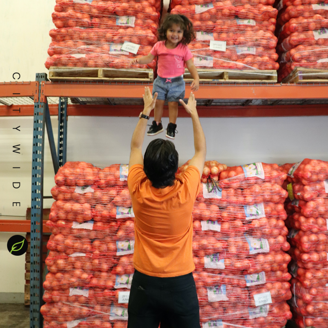 City Wide Produce's Gopal with daughter by crates of vegetables